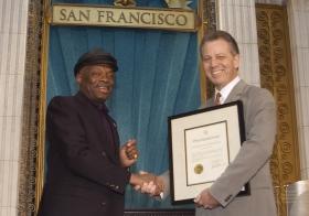 式典に出席したサンフランシスコ市のウィリー・ブラウン市長(左)は、「人種、肌の色、信条、職種を問わず、あらゆる人にとってベイエリア地区を住みよい環境にするための取り組み」を称える公式な声明を述べました。